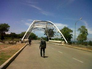 Ini adalah jembatan perbatasan antara Timor Leste dan Indonesia. Kita hanya diperbolehkan untuk berjalan kaki... untuk menuju Kantor Imigrasi dan melewati jembatan yang panjang dan panas ini.